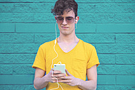 Portrait of young man listening music with smartphone and earphones in front of blue brick wall - RTBF00907