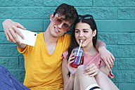 Young couple taking selfie with smartphone in front of blue brick wall - RTBF00916