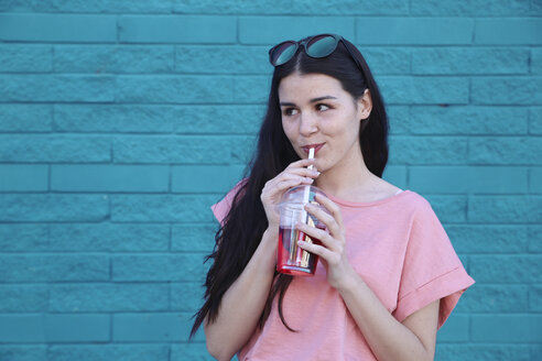 Portrait of young woman drinking soft drink - RTBF00922