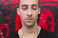 Portrait of pierced man with eyes closed - MGIF00004