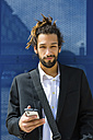Portrait of young businessman with dreadlocks using smartphone - MGIF00013