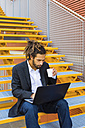 Young businessman with dreadlocks sitting on stairs using laptop - MGIF00016