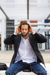 Portrait of young businessman with dreadlocks listening music with headphones and cell phone - MGIF00022