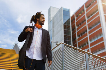 Young businessman with dreadlocks walking downstairs - MGIF00025