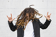 Young businessman tossing his dreadlocks showing Rock And Roll Sign - MGIF00031