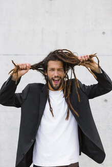 Portrait of young businessman with dreadlocks pulling funny faces - MGIF00034
