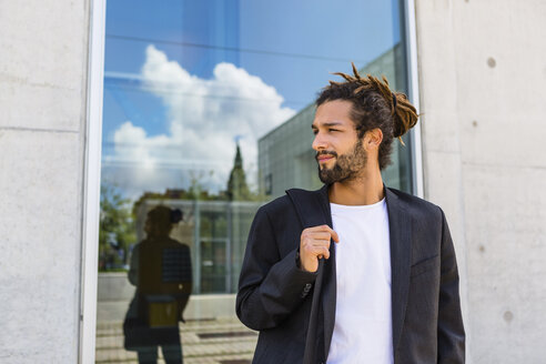 Portrait of young businessman with dreadlocks waiting in front of building - MGIF00037