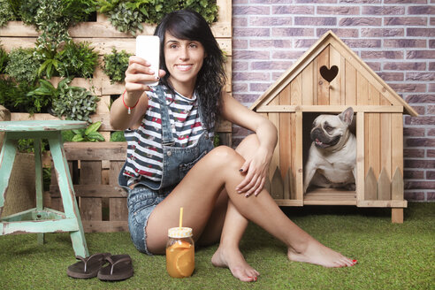 Woman and french bulldog taking a selfie on the terrace - RTBF00924