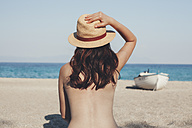Greece, young woman on the beach looking at the sea - BZF00370