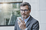 Portrait of businessman speaking voice mails on his smartphone - RORF00975