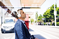Businessman with headphones waiting at the bus stop - HAPF01747