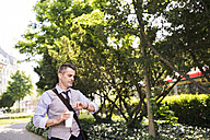 Mature businessman with coffee in city park checking the time - HAPF01753