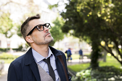 Mature businessman in city park looking up - HAPF01759