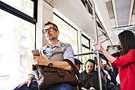 Businessman with smartphone and earphones travelling in tram - HAPF01765
