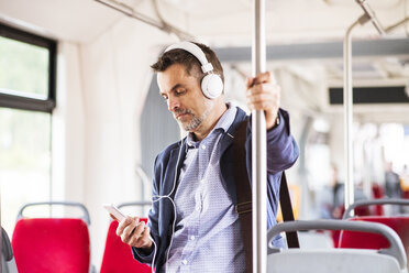 Businessman with smartphone and headphones travelling by bus - HAPF01771