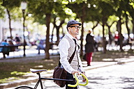 Mature businessman on bicycle in the city - HAPF01780