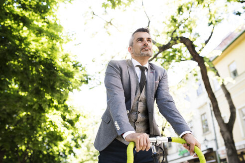 Mature businessman on bicycle in the city - HAPF01786