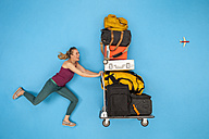 Woman pushing luggage trolley - BAEF01388