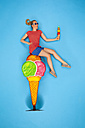 Woman sitting on big icecream cone, eating a small one - BAEF01499