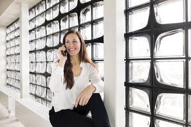 Portrait of smiling businesswoman on the phone - DMOF00022