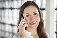 Portrait of smiling businesswoman on the phone - DMOF00025