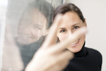 Reflection and portrait of smiling businesswoman showing victory sign - DMOF00028