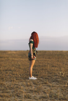 Redhaeded woman standing on a meadow - JPF00236