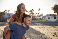 Young man giving his girlfriend a piggyback ride on the beach - PACF00016