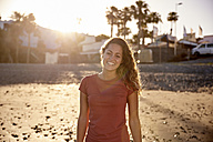 Portrait of happy woman on the beach at evening twilight - PACF00025