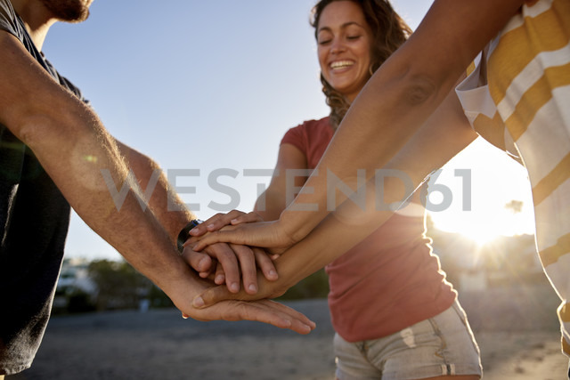 Three friends joining hands on the beach - PACF00028