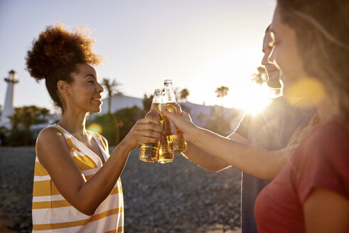 Three friends toasting with beer bottles on the beach at sunset - PACF00031