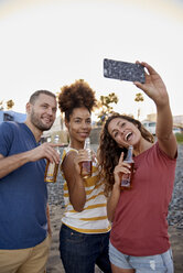 Three friends with beer bottles taking selfie on the beach - PACF00043