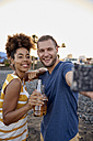 Two friends with beer bottles taking selfie on the beach - PACF00046