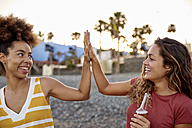 Two best friends high fiving on the beach - PACF00052