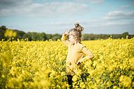 Girl standing in rape field looking out - MOEF00018