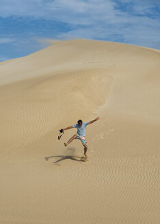 Australia, Port Lincoln, man running down sand dune - TOVF00082