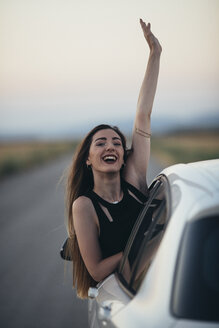 Happy woman leaning out of car window - JPF00246