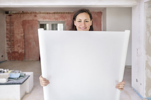 Smiling woman in empty apartment holding plan - DMOF00032