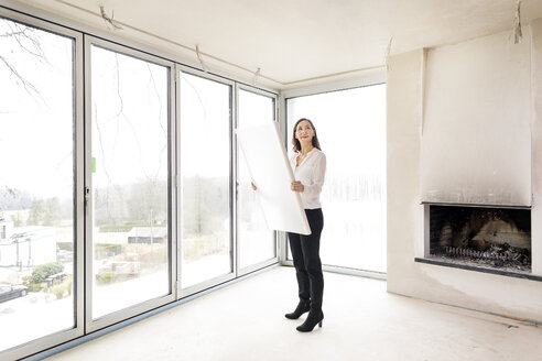 Woman in empty apartment with plan - DMOF00035