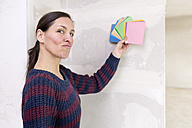 Woman in new home pouting holding color sample - DMOF00038