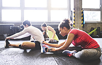 Three young people stretching in gym - HAPF01791