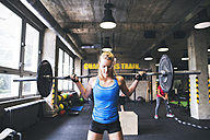 Young woman lifting barbell in gym - HAPF01809