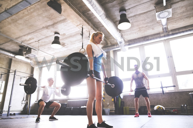 Young woman with training partners lifting barbell in gym - HAPF01815
