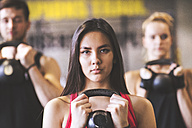 Confident young woman with training partners lifting kettlebell in gym - HAPF01833