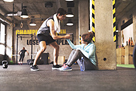 Athlete helping young woman getting up after a break in gym - HAPF01836