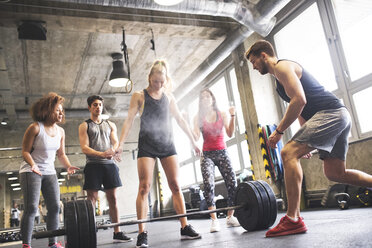 Group of young fit people cheering at woman weightlifting in gym - HAPF01839