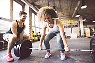Young woman with training partner preparing to lift barbell in gym - HAPF01851