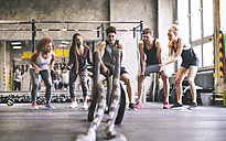Group of young fit people cheering at man exercising with ropes in gym - HAPF01857