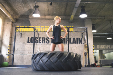 Young woman exercising with tractor tyre in gym - HAPF01860