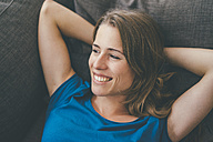 Smiling young woman lying on couch at home - KNSF01657